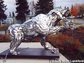 Side view of bear made of chrome car bumpers.