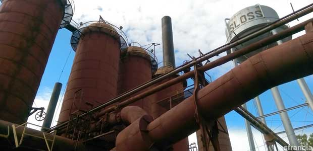 Rust-red tanks and pipes, and silver water tower, of giant outdoor former ironworks furnaces.