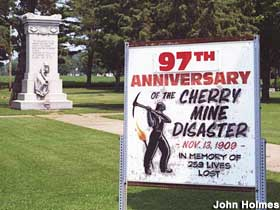 Sign notes anniversary of the Cherry Mine Disaster with monument in background.