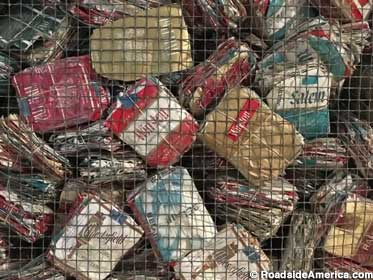 Mesh bin holds 108,000 cigarette packs saved by a delusional patient.