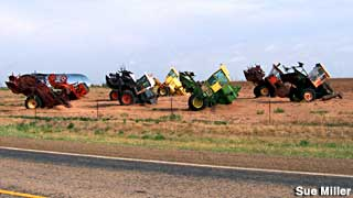 Tractors half-buried, Cadillac Ranch style.