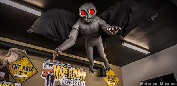 Mothman costume hangs from the museum ceiling, with a gray body, large black wings, hands with claws, a skull-like head, and glowing red eyes. He looks more like a man than a moth.
