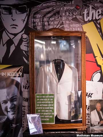 White sport coat in a glass display case.