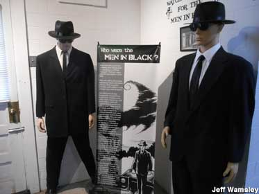 Two dummies wearing black suits, hats, and sunglasses, identified as
