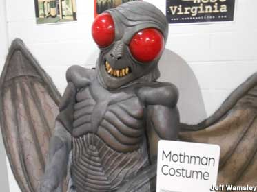 Mothman costume stands upright, with a gray body and wings, pointy teeth, and bulging red eyes.